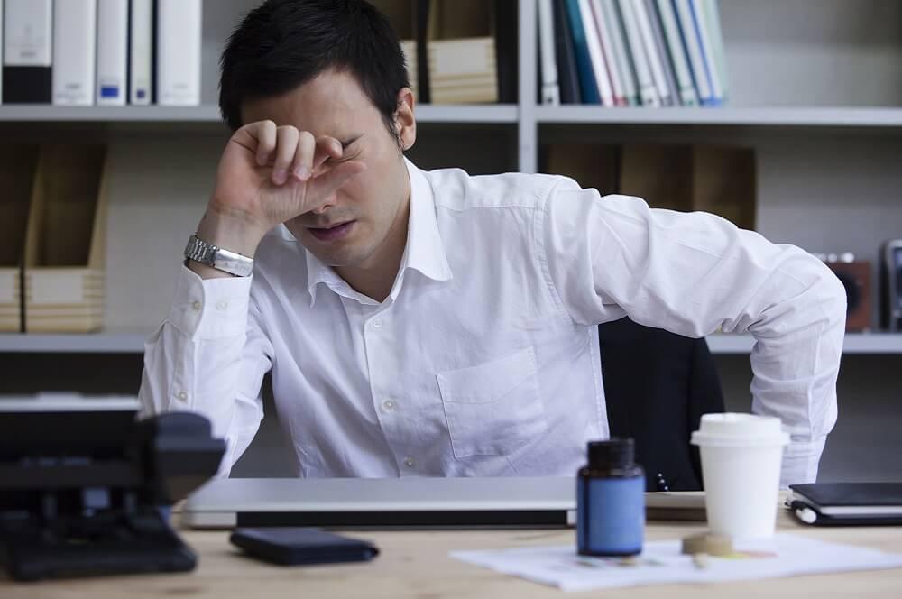 過重労働によって疲労している人のイメージ